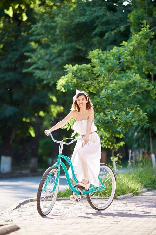 Den härliga kvinnan i vita blått för klänningridningtappning cyklar i en parkera royaltyfria bilder