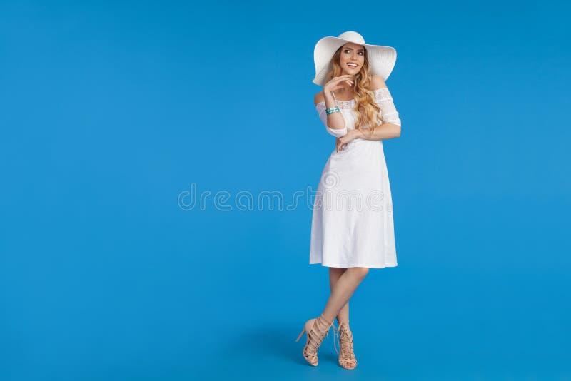 Den härliga kvinnan i den vita klänning- och solhatten står med handen på Chin And Looking Away royaltyfria foton