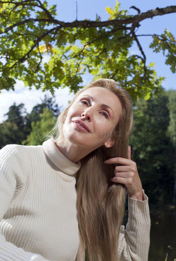 Den härliga kvinnan kammar långt hår i sommardagen på flodbanken royaltyfri bild