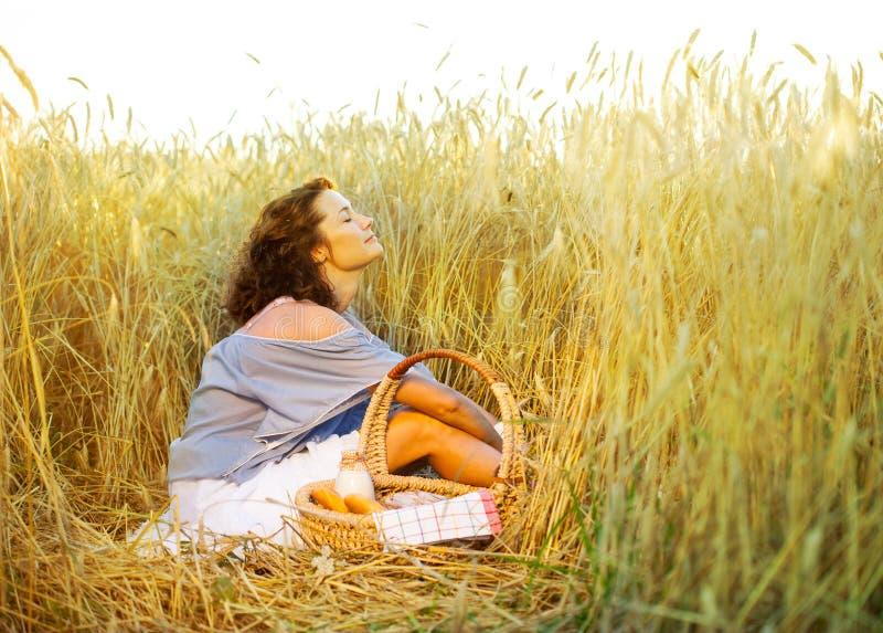 Den härliga kvinnan kopplar av i ett fält bland veteöron royaltyfri fotografi
