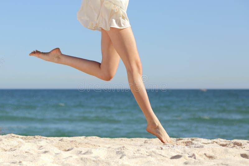 Den härliga kvinnan lägger benen på ryggen länge banhoppning på stranden arkivfoto