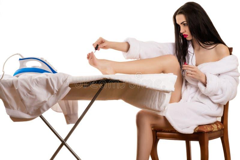 Den härliga kvinnan målar spikar på foten royaltyfri fotografi