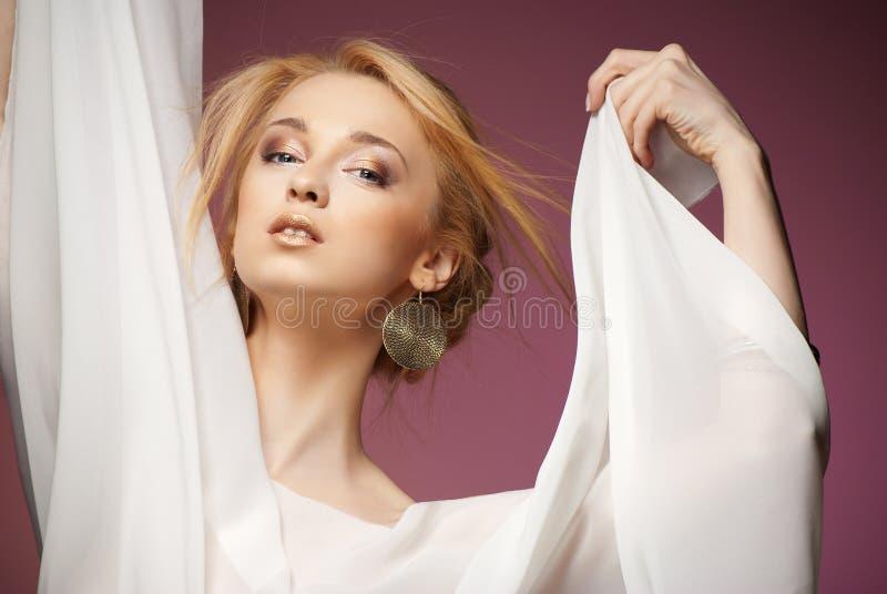 Den härliga kvinnan med armar draperade i vit chiffong royaltyfri foto