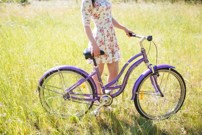 Den härliga kvinnan med cykeln på staden parkerar härlig natur arkivfoton