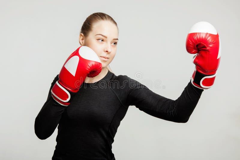 Den härliga kvinnan med de röda boxninghandskarna slår attraktiv kvinnlig boxareutbildning för apercote arkivfoton
