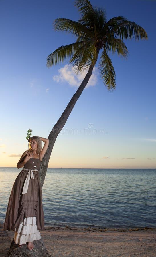 Den härliga kvinnan med en ros på en palmträd tahiti royaltyfri foto