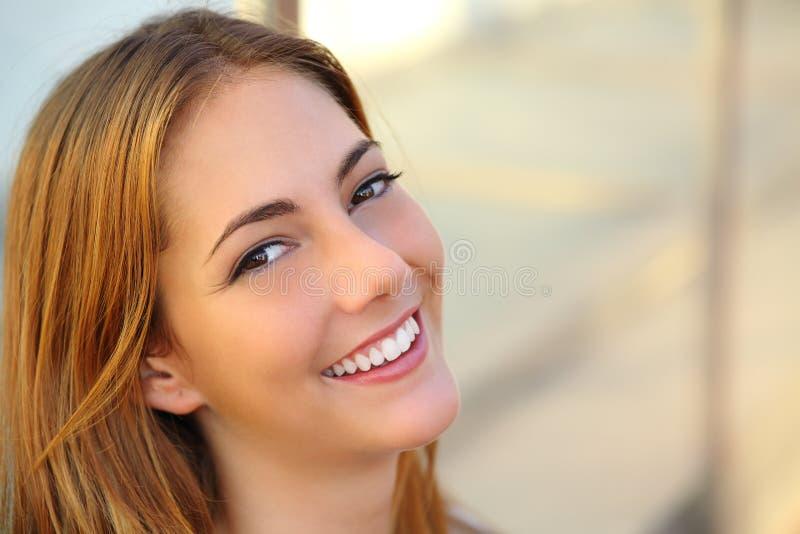 Den härliga kvinnan med ett perfekt vitt leende och slätar hud royaltyfri bild