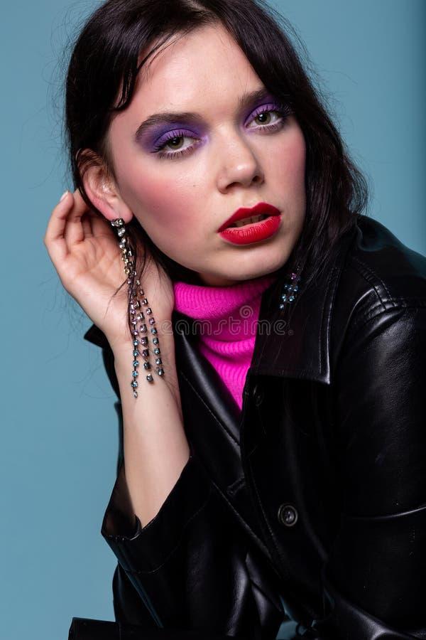 Den härliga kvinnan med färgrik makeup sätter en hand till örat fotografering för bildbyråer