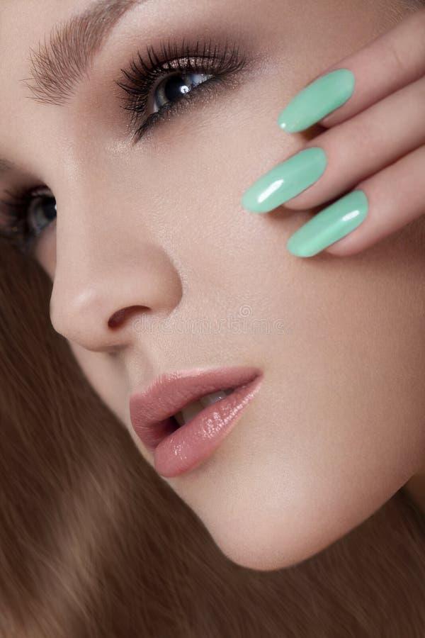 Den härliga kvinnan med färgrikt spikar och lyxig makeup. Härlig flickaframsida royaltyfri fotografi