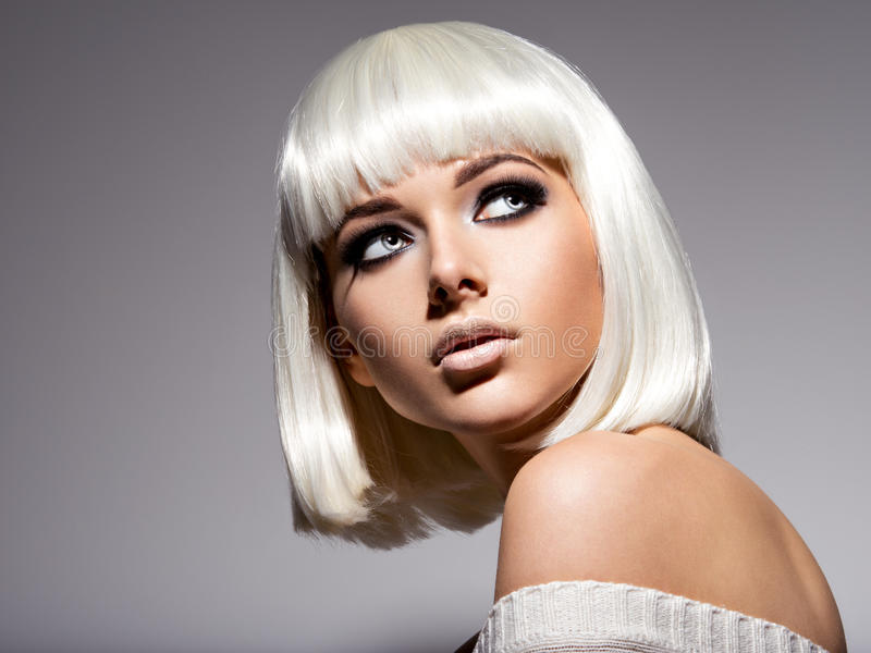 Den härliga kvinnan med frisyren guppar och danar svart makeup av royaltyfri fotografi