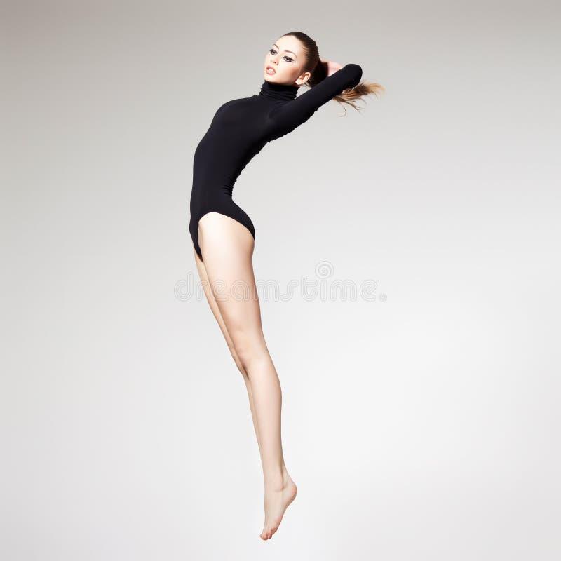 Den härliga kvinnan med görar perfekt slankt förkroppsligar och lägger benen på ryggen long banhoppning - f royaltyfri fotografi