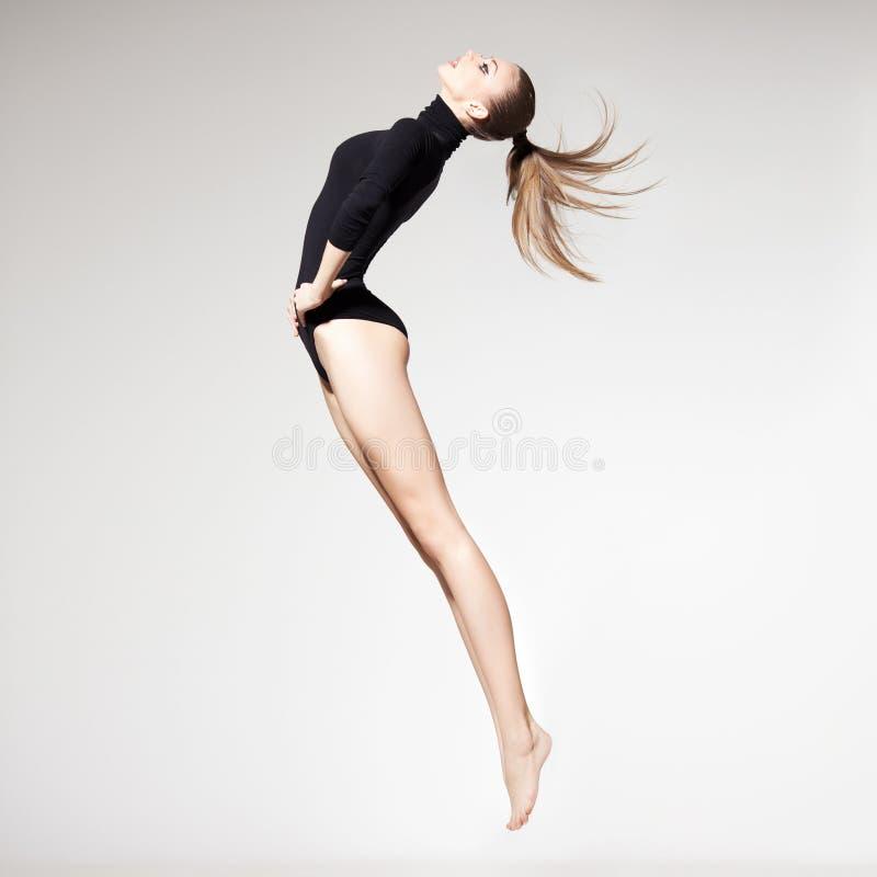 Den härliga kvinnan med görar perfekt slankt förkroppsligar och lägger benen på ryggen long banhoppning - f royaltyfria bilder