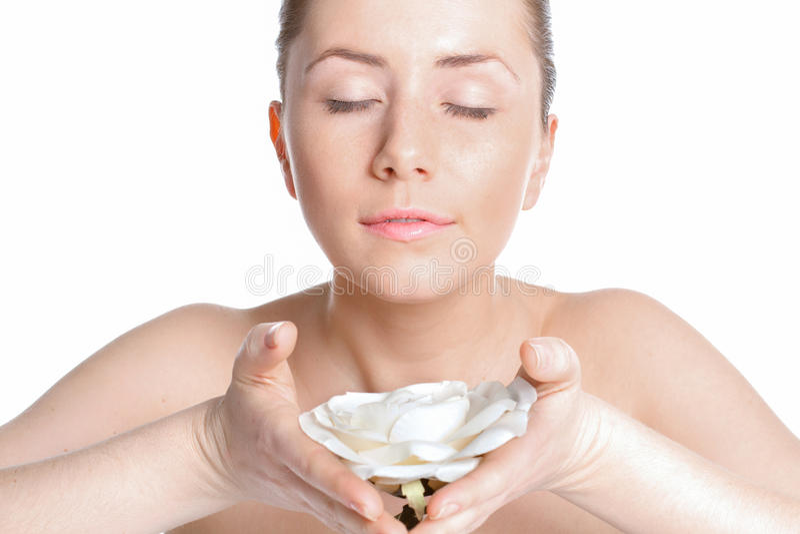 Den härliga kvinnan med klar hud inhalerar doften av rosor arkivfoto