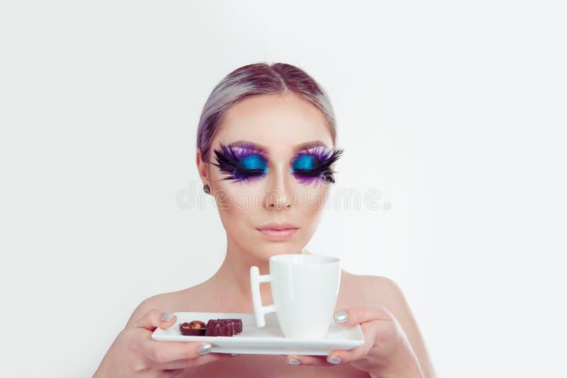 Den härliga kvinnan med den konstnärliga purpurfärgade makeupfjädern för blåa ögon på ögonfrans synar den stängda hållande koppen arkivbilder