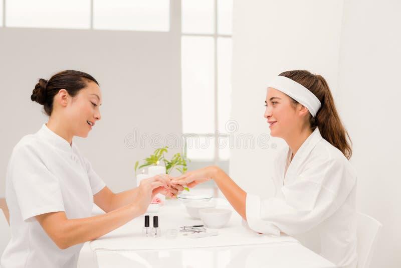 Den härliga kvinnan med kosmetologen som att applicera spikar fernissa till kvinnliga klienter, spikar arkivbilder