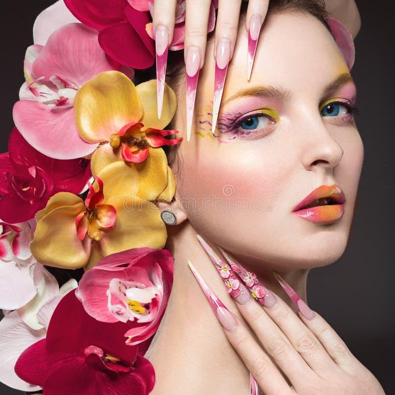 Den härliga kvinnan med länge spikar, gör perfekt hud, hår av orkidér arkivbilder