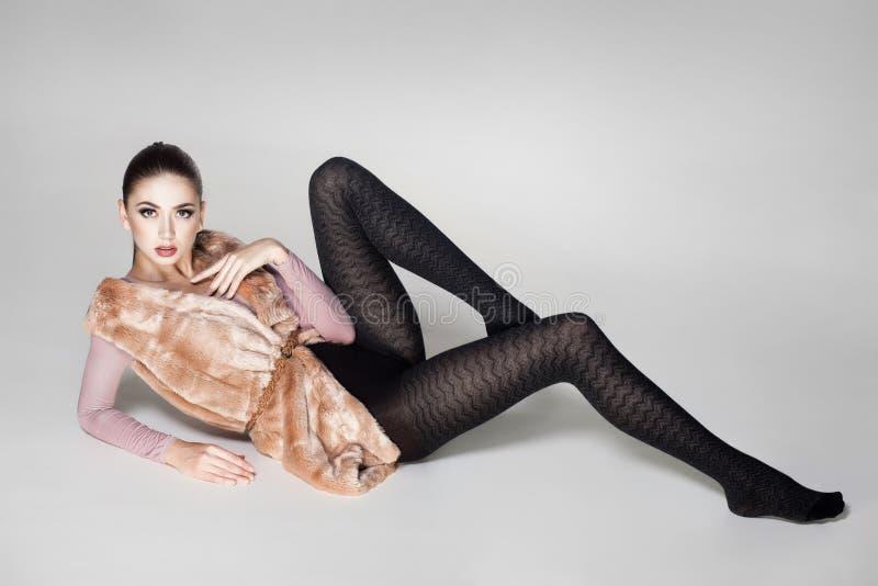 Den härliga kvinnan med långa sexiga ben klädde elegant posera royaltyfri fotografi