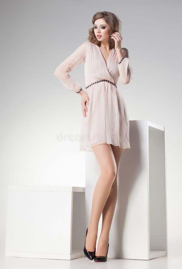 Den härliga kvinnan med långa sexiga ben klädde retro elegant posera i studion royaltyfria bilder