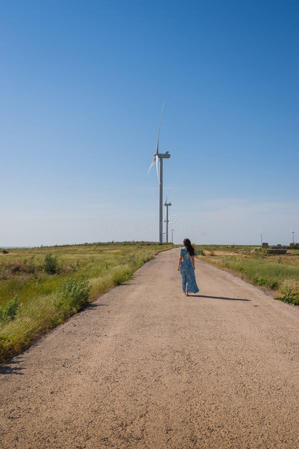 Den härliga kvinnan med långt hår i en blå klänning går på vägen mellan gröna fält och vindturbiner på blå himmel royaltyfria bilder