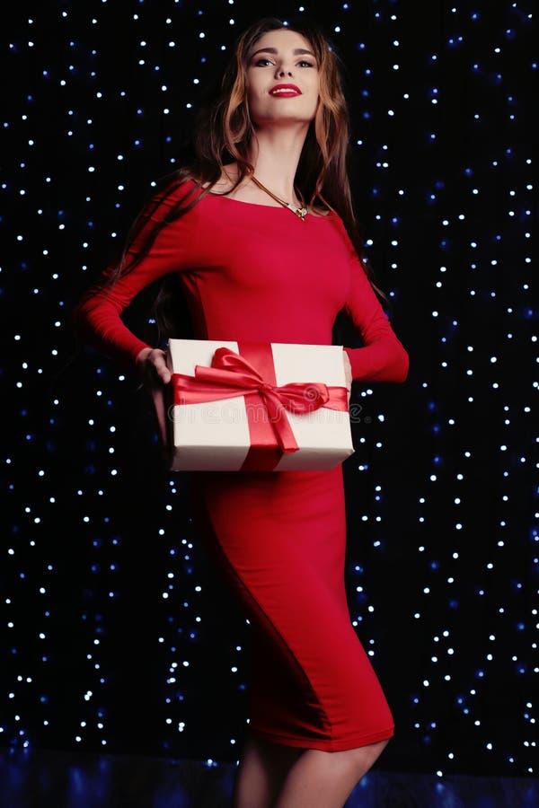 Den härliga kvinnan med mörkt lockigt hår bär den eleganta röda klänningen och smycket royaltyfria bilder