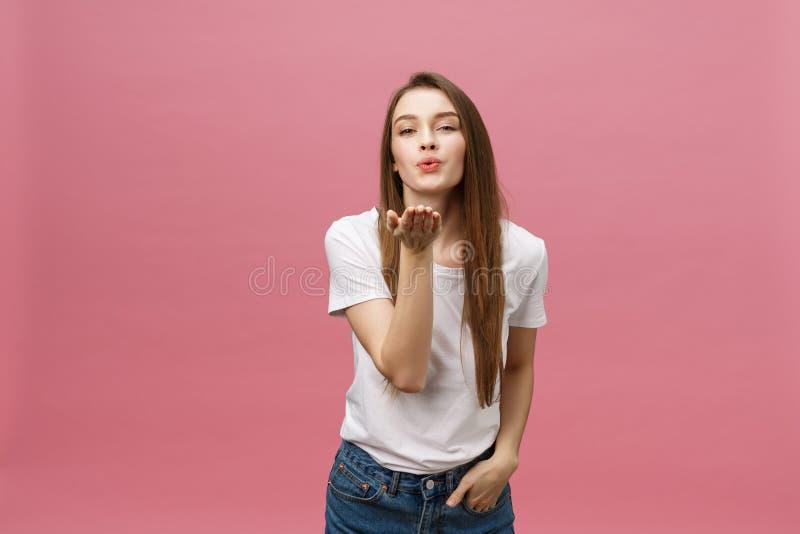 Den härliga kvinnan med makeup och långt blont hår blåser kyssen, visar hennes bra känslor, säger farväl på avstånd fotografering för bildbyråer