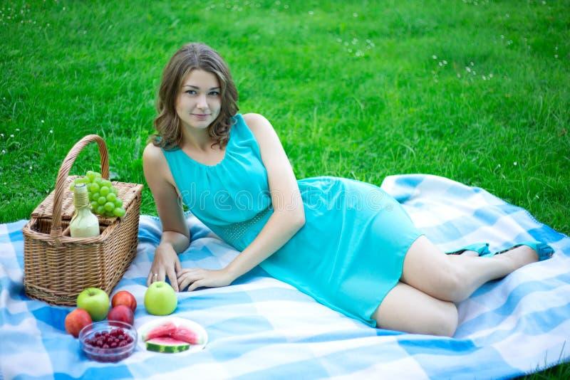 Den härliga kvinnan med picknickkorgen och frukter i sommar parkerar royaltyfria bilder