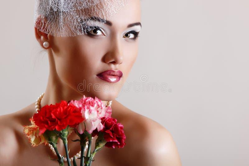 Den härliga kvinnan med rosa färger blommar den retro glamourskönhetståenden arkivfoto