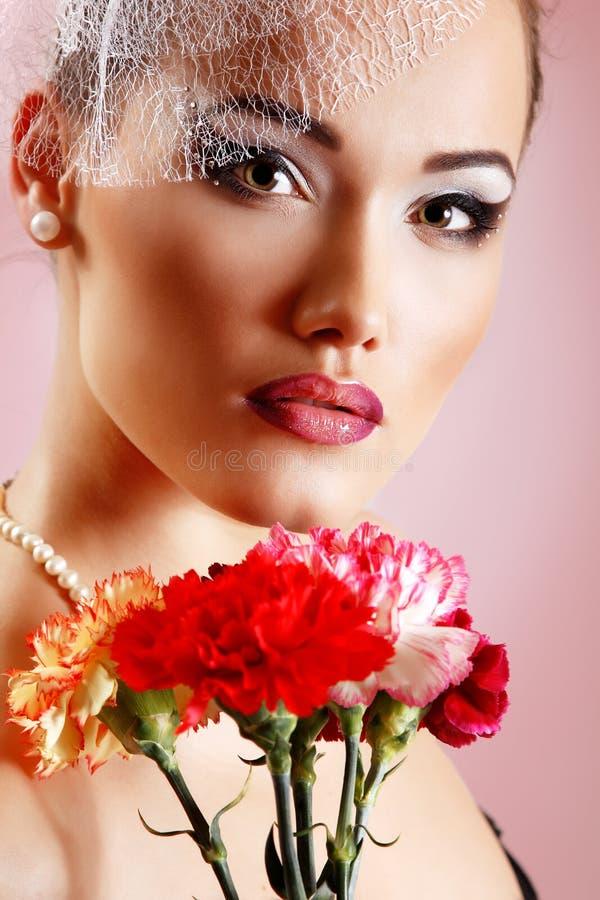 Den härliga kvinnan med rosa färger blommar den retro glamourskönhetståenden royaltyfri bild