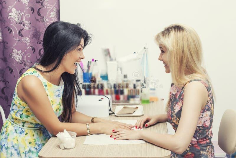 Den härliga kvinnan med skönhetsalongen klienten gör manikpur arkivbilder