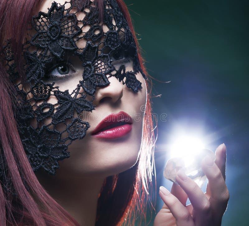 Den härliga kvinnan med snör åt maskeringen och diamanten royaltyfria bilder