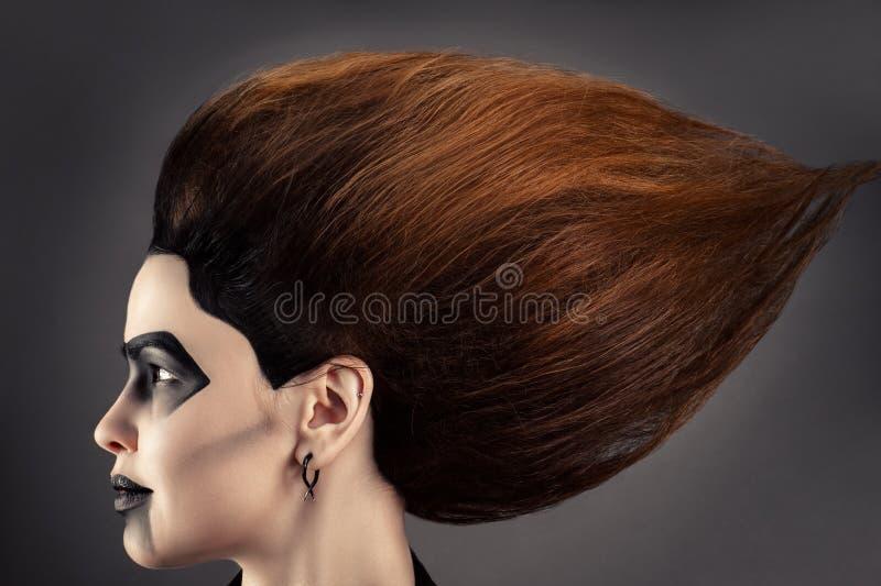 Den härliga kvinnan med storartad hår- och mörkermakeup i profil vänder mot royaltyfria foton