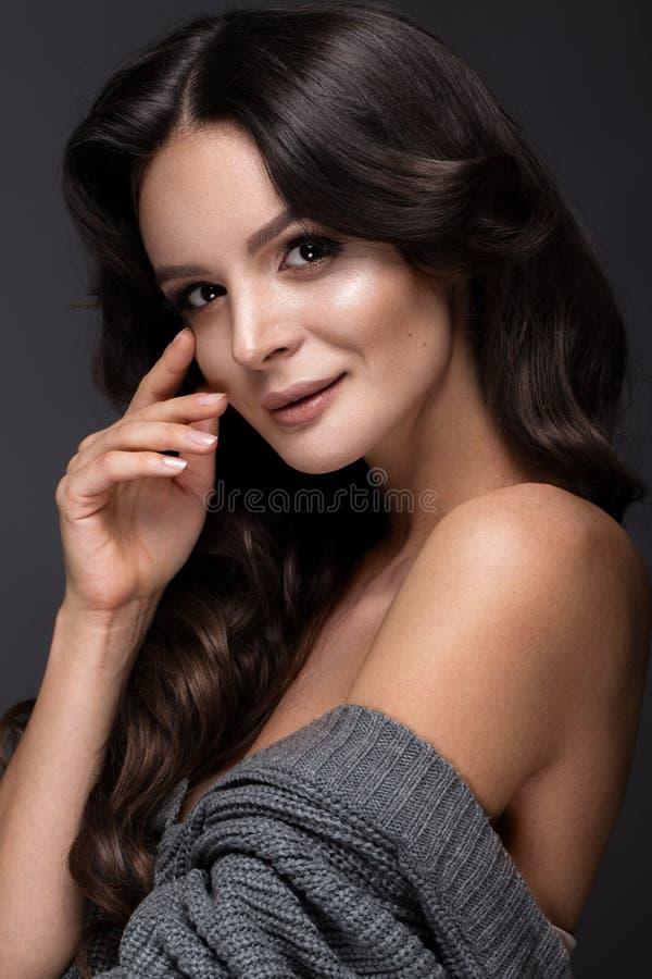 Den härliga kvinnan med sund hud och hår krullar och att posera i studio Härlig le flicka arkivfoto