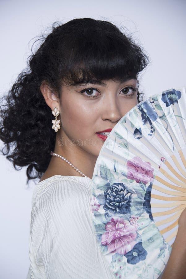 Den härliga kvinnan med svart hår och orientaliska blom- fanen med örhängen och vit snör åt klänningen som modellerar ståenden royaltyfria bilder