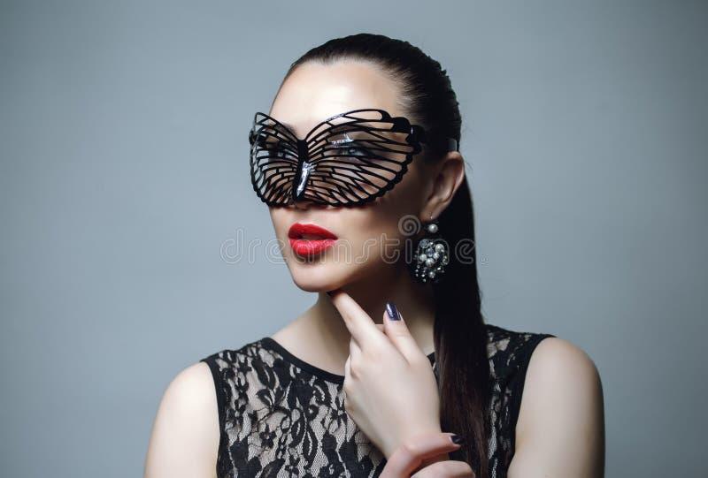 Den härliga kvinnan med svart snör åt maskeringen över henne ögon Röda sexiga kanter och spikar closeupen royaltyfria foton