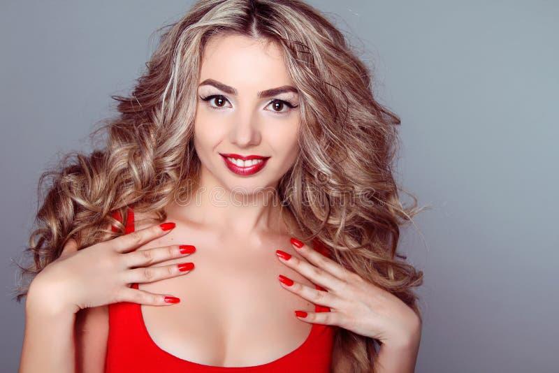 Den härliga kvinnan med wavy hår och den röda manicuren spikar på grå färgba royaltyfria foton
