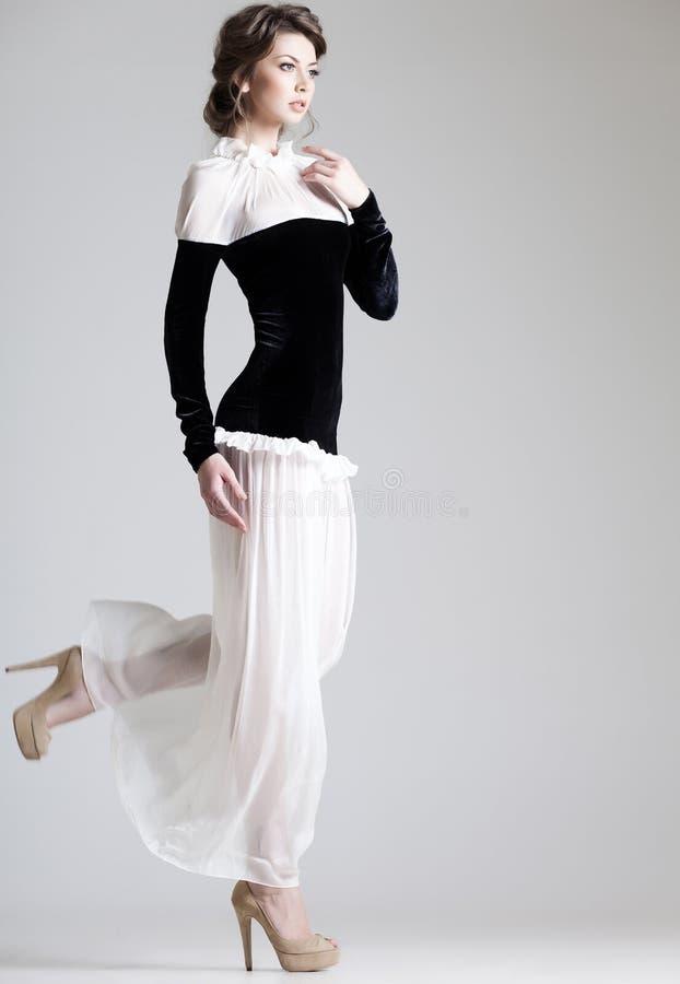 Den härliga kvinnan modellerar att posera i elegant klänning i studion arkivfoton