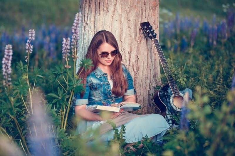 Den härliga kvinnan nära trädet och fältet med lupine läser en bok fotografering för bildbyråer