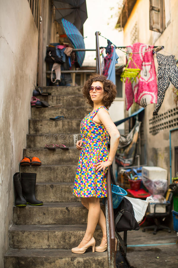 Den härliga kvinnan på solglasögon står hänsynsfullt i ett fattigt område arkivbild
