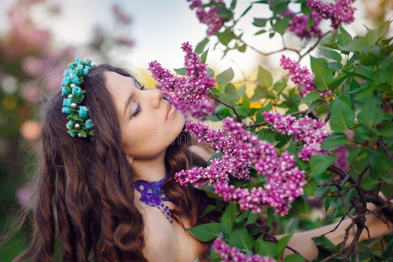 Den härliga kvinnan parkerar på våren, lukten av lilor royaltyfri fotografi
