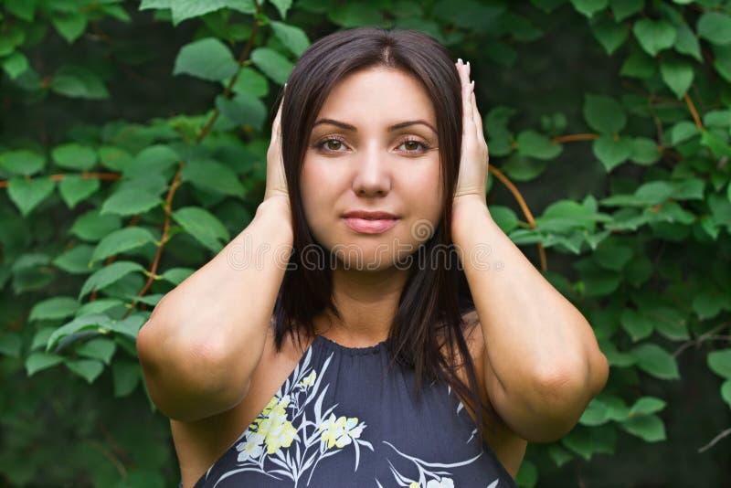 Den härliga kvinnan räknar henne händer över henne öron royaltyfria foton