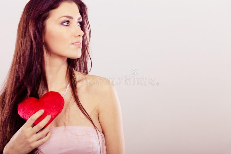 Den härliga kvinnan rymmer röd hjärta royaltyfri bild