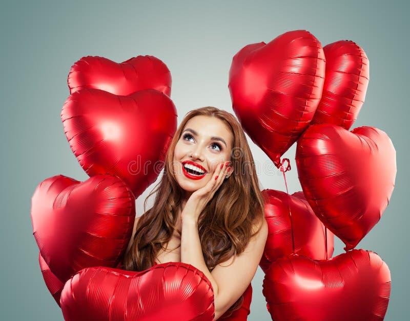 Den härliga kvinnan rymmer röda hjärtaballonger Överraskning, valentin folk och valentin dagbegrepp Uttrycksfulla ansiktsuttryck royaltyfri bild