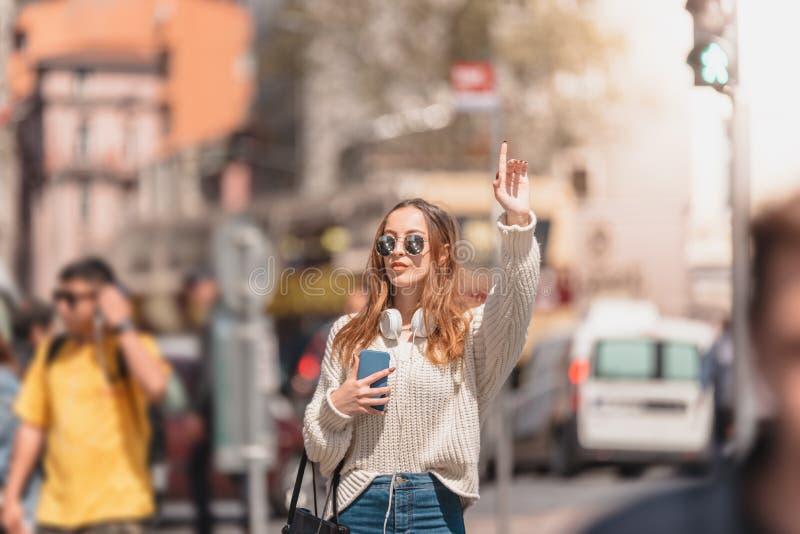Den härliga kvinnan söker efter en taxi på gatan royaltyfria bilder