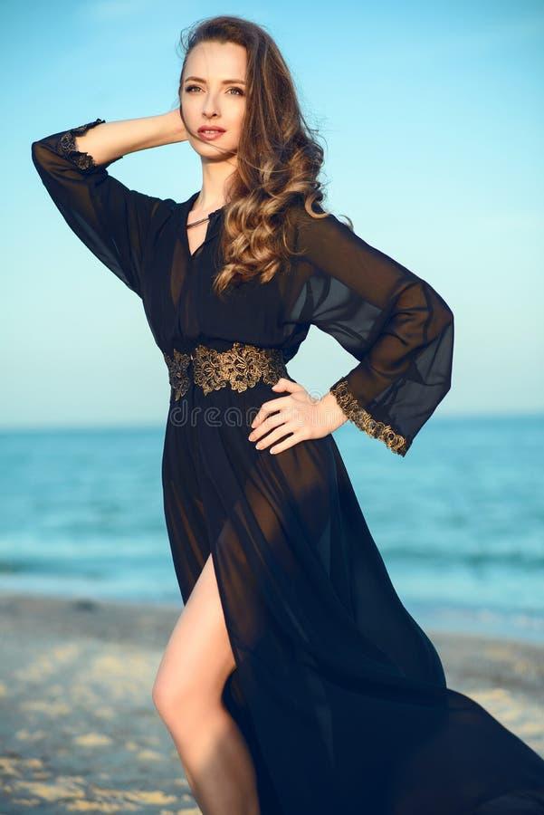 Den härliga kvinnan som bär den orientaliska svarta chiffongstranden för moderiktig chiffong, täcker upp att stå på stranden royaltyfria bilder