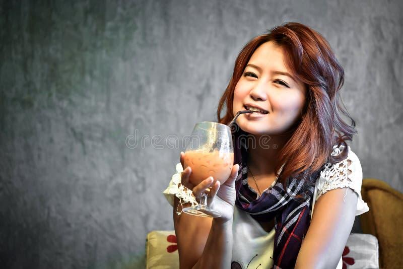 Den härliga kvinnan som dricker is, mjölkar te royaltyfri bild