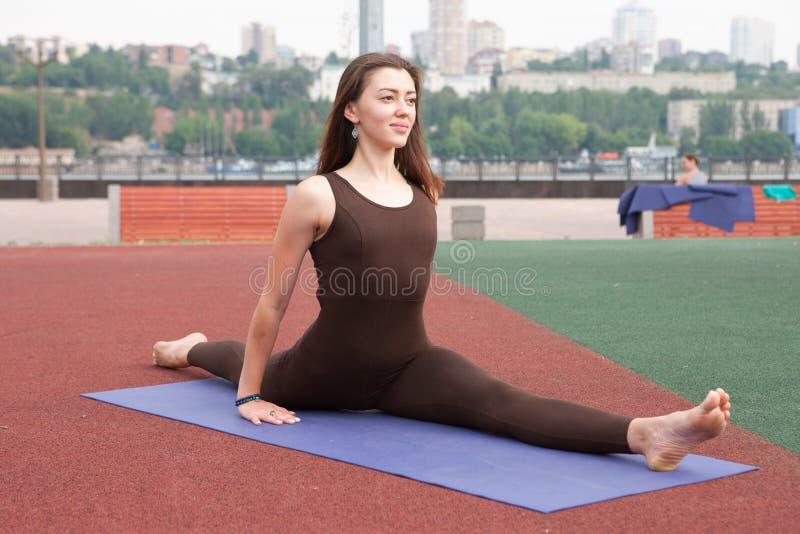 Den härliga kvinnan som gör Vriksasana, poserar på yogagrupp royaltyfria foton