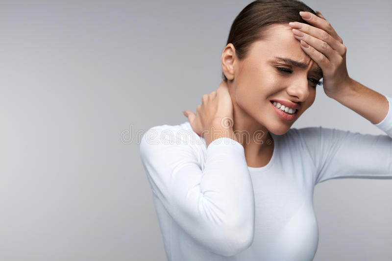 Den härliga kvinnan som känner sig sjuk och att ha huvudvärk, den smärtsamma kroppen, smärtar royaltyfria foton
