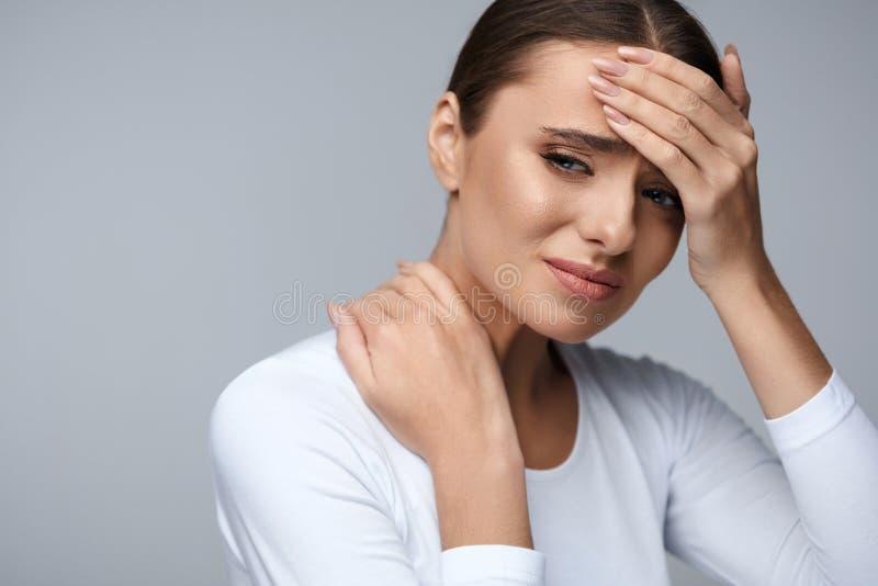 Den härliga kvinnan som känner sig sjuk och att ha huvudvärk, den smärtsamma kroppen, smärtar arkivfoto