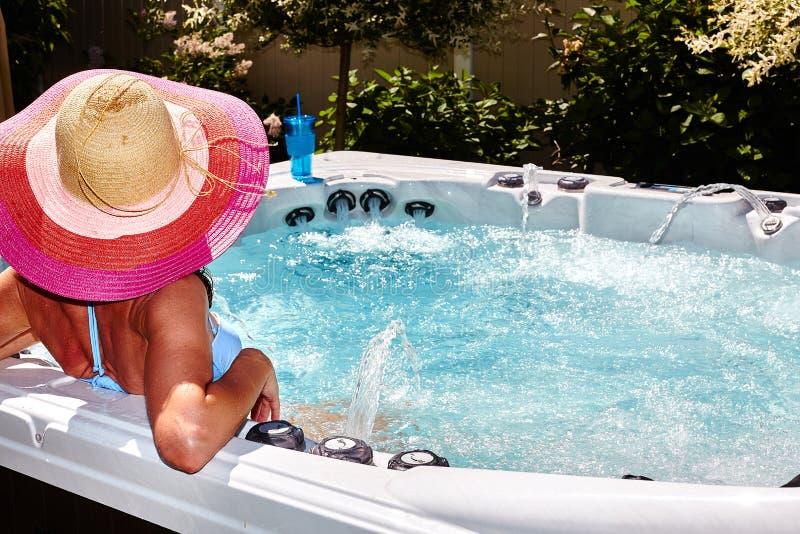 Den härliga kvinnan som kopplar av i varmt, badar arkivbild