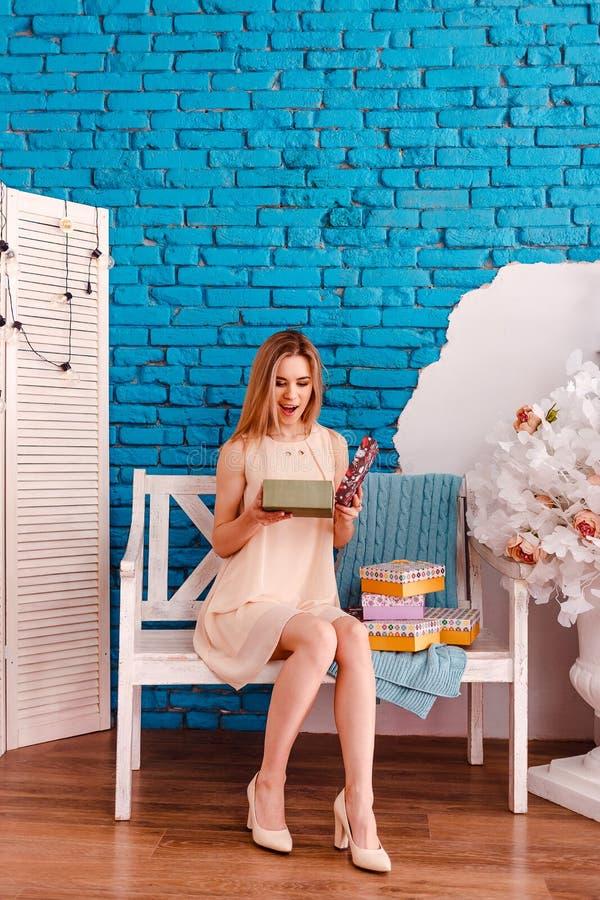 Den härliga kvinnan som sitter på en bänk i rummet och, öppnar gåvakartongerna royaltyfri bild